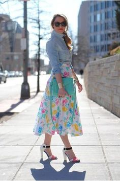 A midi-length pastel floral skirt pairs perfectly with a tied chambray shirt and matching clutch.