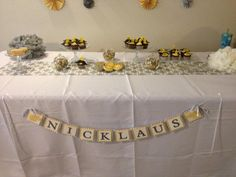 Theme was yellow and grey. Greek pattern runner in grey sugar cookies  yellow n grey M&Ms with the baby's name and says its a boy Cupcakes made by me  Fondant toppers baby bottles and mustache made by me -raquel
