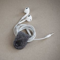 Handmade Wool Felt Cable Holder by Oker. Made of 100% wool felt, a non-woven textile that is produced by condensing and pressing fibres together. Holds all kinds of cables and headphones. 3cm X 9cm X 0.2cm. Please allow 2-3 weeks for delivery