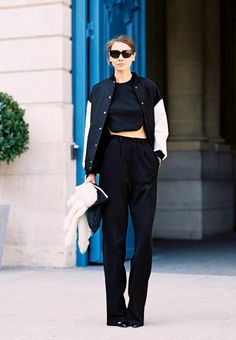 A black crop top is worn with a bomber jacket, high-waisted pants, and heels