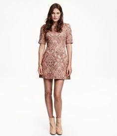 Fitted dress in brocade with a sheen. Seam at waist, concealed back zip, and short sleeves. Lined.