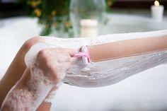 Woman shaving her legs in bathtub