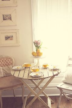 Yellow tea cups and lemons on white.  I would love a breakfast corner like this one day!