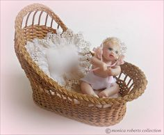 1:12th miniature wicker bassinet by Carolyn Lockwood ... sculpy baby by Elizabeth Matatucci (even has two tiny teeth), tatted edging and bonnet by Esther Hargrove.