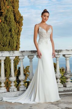 Wow your guests in this stretch satin fit and flare gown. It features beaded appliqués on an illusion bodice and a clean skirt leading to the chapel length train. This look is romantic and sexy. This style is also available in an alternate version with a crepe skirt.