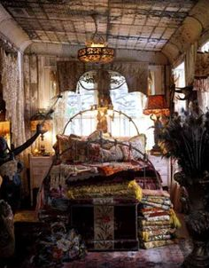 Bohemian bedroom. Eccentricity at its best, with gypsy Romanian style textiles and peacock feathers in old vintage decadent vases. Think old imperial Russia meets a gypsy caravan.