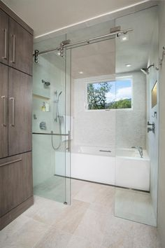 Four recessed light fixtures and a large window provide plenty of illumination in this contemporary tub and shower area. Niches in the wall offer storage space for shower essentials.
