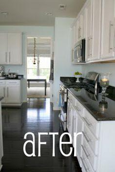 dark granite, white cabinets, dark wood floor