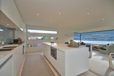 A sleek kitchen island and matching cabinets feature integrated appliances that seamlessly fit with the modern design of this kitchen. Plus, floor-to-ceiling windows offer outstanding, panoramic views of Lake Wakatipu and the surrounding mountains.