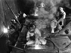 Female Welders Welding Seams on Deck Section of an Aircraft Carrier under…