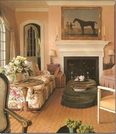 Sweet, simple.....love the peachy walls, floral sofa, upholstered ottoman/coffee table, arches, equestrian art.......nice English country