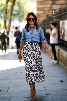 A guest wears a blue denim shirt, a zebra print skirt, sunglasses, during London Fashion Week September 2018 on September 17, 2018 in London, England.