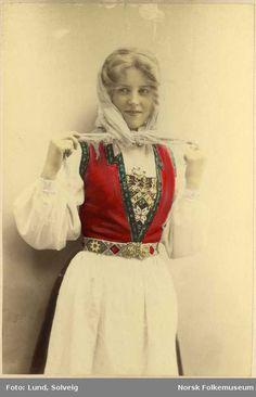 Digitalt Museum - Fargelagt portrett av ung pike i Hardangerdrakt, 3/4 figur. Holder tak i endene på skautet sitt. Fotograf: Solveig Lund