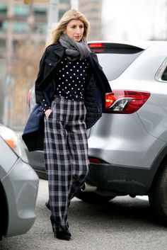 Printed sweater, plaid trousers, and a black jacket.