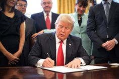 U.S. President Donald Trump signs an executive order cutting regulations, accompanied by small business leaders at the Oval Office of the White House in Washington U.S., January 30, 2017.