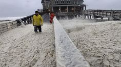 Oct. 28, 2012: A news crew wades through sea foam blown onto Jeanette's Pier in Nags Head, N.C., as wind and rain from Hurricane Sandy move into the area.Source: AP