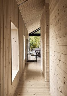 """Hallway and Medium Hardwood Floor The interior of the house is completely """"skinned,"""" as Scott puts it, in knotty spruce. A lamp from Weylandts sits atop nesting tables from James Mudge Furniture Studio."""