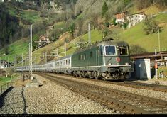 """Back in the days.... In 1997, Sisikon at Lake Lucerne is still free of any noise protecting walls. In 1997, SBB is not spilt up between """"Cargo"""" and """"Personenverkehr"""". In 1997, locomotives can be seen in front of all kind of trains. In 1997, there were no italian built trains running over Gotthard route. In 1997, Re 6/6 11686 is pulling it's Eurocity with italian coaches from Zürich to Milano, passing Sisikon and soon will climb the northern ramp of Gotthard."""