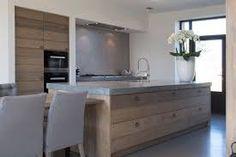 Een houten keuken met openslaande deuren naar de tuin en een ruim kookeiland met zitplaatsen om - Keuken recup ...