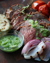 Andrew Zimmern's boneless leg of lamb is marinated with chile and lime juice and grilled with fresh herbs, then served with a tangy tomatillo salsa.