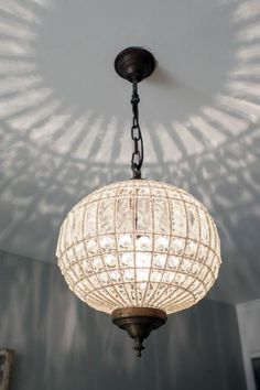 The+pendant+light+with+crystal+shade+casts+an+ornate+pattern+on+the+ceiling.