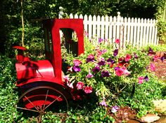 ParadeOfGardens photo of metal tin lizzy toy car in the garden filled with flowers.  Great way to create a garden accent is by adding something like this to plant your flowers in!