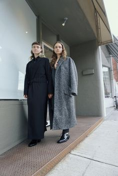 ON KATHRYN, RIGHT, HOPE VERA CHECK BLAZER ($560) AND KRISSY TROUSER ($298), AREA COAT IN BLACK MELANGE HERRINGBONE ($930) AND DANNIE LACE UP OXFORD IN BLACK SPARKLE ($640); ON GENEVE, THE CAMP COAT DRESS IN BLACK ($510) AND UNDERNEATH THE WAVE SHIRT DRESS ($478).