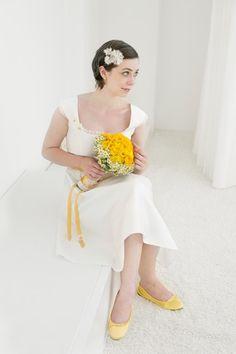 kurzes hochzeitskleid mit gelben details und gänseblümchen, carrée ausschnitt und breiten trägern, geraffter, glockig fallender rock und gelber brautstrauss mit ranunkeln