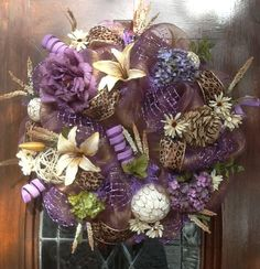 lavender and antique gold deco mesh wreath, newsprint flower, lilies and sprays of flowers as well as decorative wooden balls all through the wreath