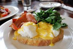 Soft poached eggs with bacon and spinach on sourdough bread