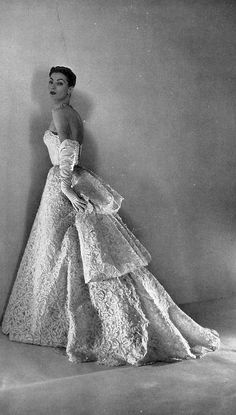 Wearing a gala evening gown of white lace in floral motif by Christian Dior, photo by Georges Saad, 1952