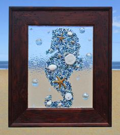 Unique beach window art by Luminosities! Seahorse made of blue colored abalone shells, starfish and sand dollars, surrounded by pale blue gems. Set in a wood frame.  Measurements are 12x14
