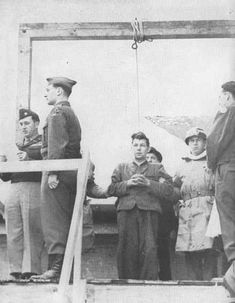 Franz Strasser, former Nazi official, is strung up for killing two American fliers who were forced down in Germany during the war. Johann Reichart, German executioner, is just visible behind him. At the far left of picture, Colonel T. N. Griffin, U.S. Third Army Provost Marshal, reads the charges against Strasser as other officers and a priest stand by.