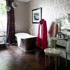herringbone wood floor, free standing tub, luscious wallpaper in bathroom