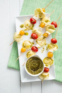 SUPER easy appetizer idea! Layer mini ravioli (or tortellini) onto skewers with cubed mozzarella and grape tomatoes. Then drizzle with pesto, or serve with a bowl of pesto on the side for dipping. Inexpensive and so quick!