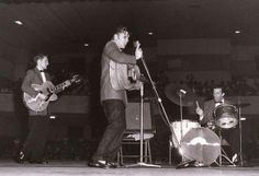Taken in May, 1956. Unknown location. Also pictured, to the left of Elvis, Scotty Moore. To the right of Elvis, DJ Fontana on drums.
