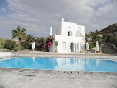 This 5 bedroom exceptionally decorated villa located in Mykonos , is in perfect harmony with its natural environment .  The exterior indicates its Cycladic architecture . It is equipped with a spectacular private swimming pool and surrounded by a natural stone-walled patio area with outdoor seating , sun beds, and a BBQ .