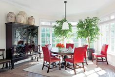 A Waldo's Designs sandblasted-glass lamp hangs in the breakfast room; antique pots are displayed atop a lattice-front mahogany china cabinet, and dining chairs in a punchy red leather surround the walnut table.
