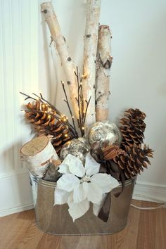 Bucket with Christmas ornaments and, sticks, and pinecones