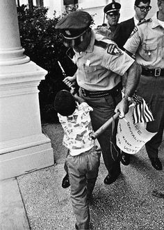 In at Jackson, Mississippi, Matt Herron took an iconic and ironic image from the civil rights era as a white policeman rips an American flag away from a young black boy, having already conf… Black History Facts, Black History Month, World History, Don Delillo, Kings & Queens, By Any Means Necessary, Iconic Photos, Famous Photos, Young Black
