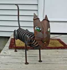 """I've made it from  of """"stuff"""" I've collected over the years. The face is one of my old shovels with green glass eyes and old welding rod for whiskers. The cat's body is an old auto coil spring. For the legs I got out the forge and tapered some round stock and then coiled the ends.  The cat measures (approximately) 22 inches long, and is 21 inches high to the top of the tail, it is 14 inches wide at the whiskers. The body is 11 inches high and 6 inches wide. The face is 12 X 7 inches."""