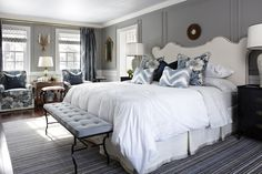 Elegant bedroom with Sarah Richardson Design Vanessa Headboard, & Kitty Chairs, gray walls, wainscoting painted Para Paints Elegant Boutique, glossy black Jamie Alexander Nightstands, Lee Joffa Zig Zag Pillows, iron bench with baby blue linen tufted cushion and striped rug