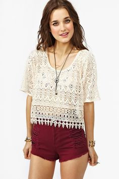 White crochet shirt and burgundy shorts.