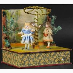 Manufacturer: Unbekannt - Unknown  Kind of toys: Tin Automata  Item-Nr.: 3 Mädchen Maibaum  Year: ca. 1900  Size: (LxWxT in inch)   Results: B Z2 1.708,00 2014   Description: Three girls at may pole, made in Germany, three German bisque head girls with blue glass eyes and open mouths, brown wigs, original dresses, on wood and composition bodies, when cranked, the dolls rotate on circular base around a May Pole, on paper over wood base with painted village background.
