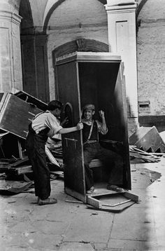 Two men playing and laughing in a confessional on the street // David Seymour Guernica, War Photography, Monochrome Photography, Spanish War, Barcelona, Dark House, Civil War Photos, Political Events, Male Poses