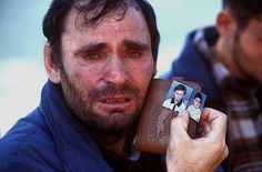 Albanian Mustafa Xaja, from the town of Mitrovica in Kosovo, shows pictures of his two children he fears to have been killed by Serbs. 1999. Peter Turnley