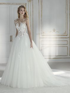 Spectacular wedding dress with two-piece effect. On the one hand, a majestic full skirt in tulle. And on the other, a bodice in embroidered tulle with guipure appliqués and sparkly beading that rises from the V-shaped waist. The bodice comes with a detachable lining. A design that hugs the body like a second skin, blending the fabrics with the silhouette.