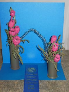 """""""Slinky,""""  8"""" design for """"Back to the Fifties"""" 2014 FDFGC show.  Painted poppyseed pods, artemesia, wire.  Blue ribbon and Past Presidents' plaque. By Jan Krass"""