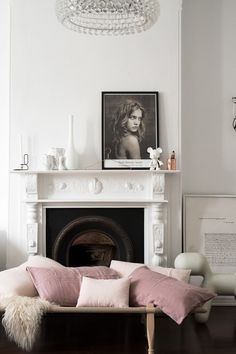 Scandinavian living space with a fireplace, a framed vintage poster, a bubble chandelier, and a wooden daybed covered in pink linen throw pillows