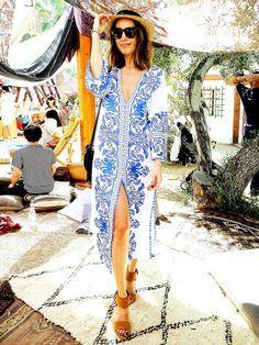 Die britische TV-Moderatorin Louise Roe in einer blau-weiß-gemusterten Tunika mit Strohhut.